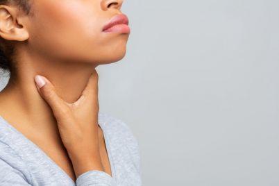 black-woman-touching-her-neck-having-pain-in-UK647JP.jpg