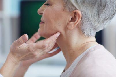doctor-examining-neck-of-senior-woman-3STB5ZL.jpg