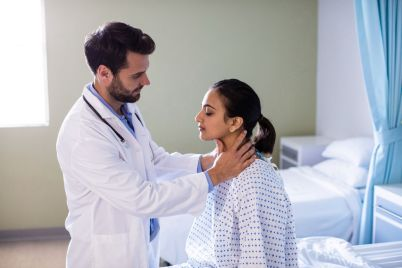doctor-examining-patients-neck-in-hospital-UG85LWH.jpg