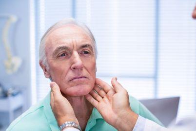 doctor-examining-senior-patients-neck-RSV74GF.jpg